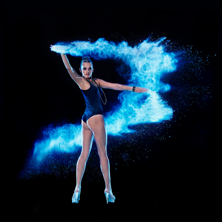 strew: Young woman jumping in blue powder cloud on black background