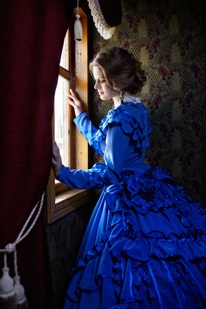 Young woman in blue vintage dress late 19th century standing near window in coupe of retro railway train Foto de archivo