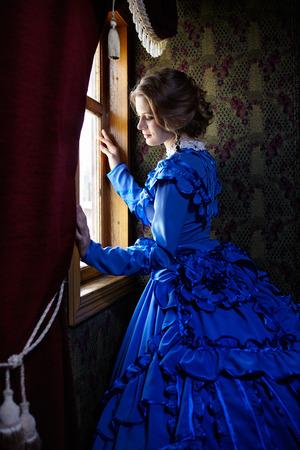 Mulher nova no vestido azul do vintage do final do século 19 em pé perto de uma janela no coupe de um trem retro