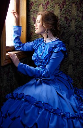 青いビンテージ ドレス レトロな鉄道のクーペで窓の外見ている 19 世紀後半の若い女性