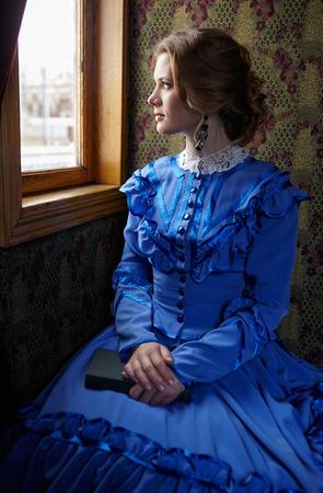 Jonge vrouw in blauwe vintage jurk late 19e eeuw zitten met boek in de coupe van retro spoorweg trein en kijkt uit het raam