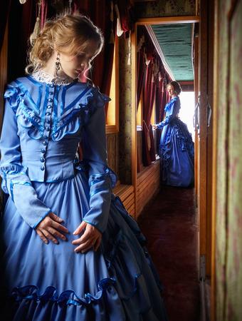 Jonge vrouw in blauwe vintage jurk late 19e eeuw die zich dichtbij venster in de gang van retro spoorvoertuig