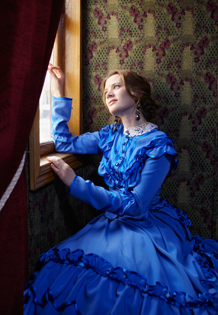 19th century: Young woman in blue vintage dress late 19th century looking out the window in coupe of retro railway train Stock Photo