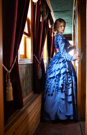 19th century: Young woman in blue vintage dress late 19th century standing near window in corridor of retro railway vehicle