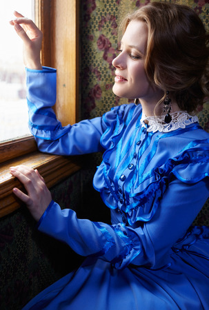 the caucasian beauty: Young woman in blue vintage dress late 19th century looking out the window in coupe of retro railway train Stock Photo