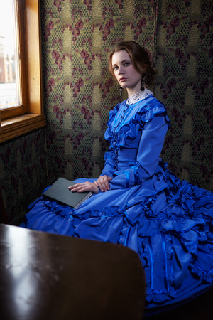 19th: Young woman in blue vintage dress late 19th century sitting with book in coupe of retro railway vehicle