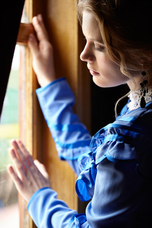 the 19th century: Young woman in blue vintage dress late 19th century standing near window in coupe of retro railway vehicle