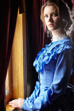 vestidos antiguos: Mujer joven en azul vestido de época tardía de pie siglo 19 cerca de la ventana en el coupé de vehículo de ferrocarril retro Foto de archivo