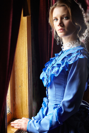 Young woman in blue vintage dress late 19th century standing near window in coupe of retro railway vehicle