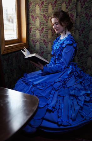 19th century: Young woman in blue vintage dress late 19th century reading the book in coupe of retro train