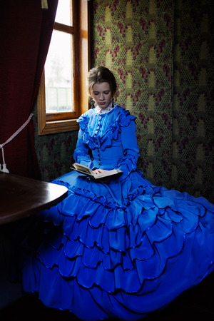 19th: Young woman in blue vintage dress late 19th century reading the book in coupe of retro train