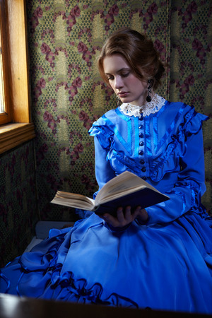 Young woman in blue vintage dress late 19th century reading the book in coupe of retro train