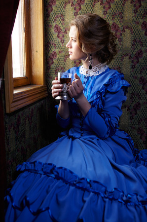 19th century: Young woman in blue vintage dress late 19th century sitting in coupe of retro railway train, looking out the window and drinking tea