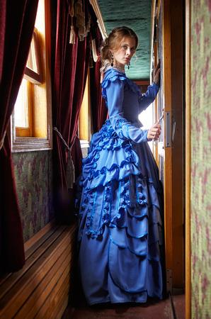 レトロな鉄道車両の廊下の窓の近く青いビンテージ ドレス 19 世紀後半の立っている若い女性