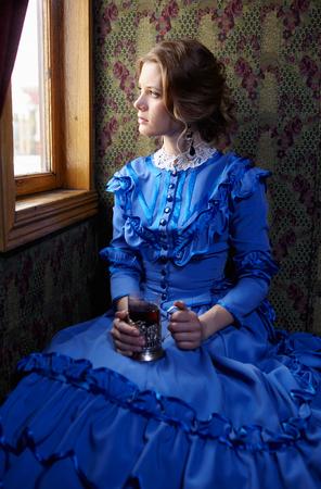 青いビンテージ ドレス レトロな鉄道のクーペに座って、窓の外見て、お茶を飲み、19 世紀後半の若い女性 写真素材