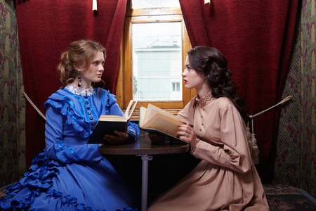 compartment: Two sisters in retro dress reading books in train compartment