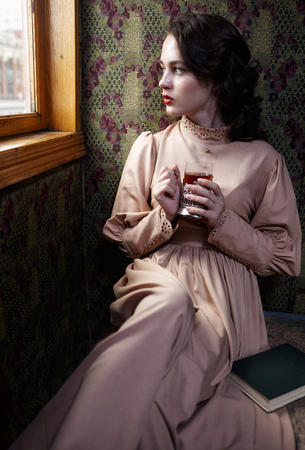 20th century: Young woman in beige vintage dress of early 20th century drinking tea in coupe of retro railway train
