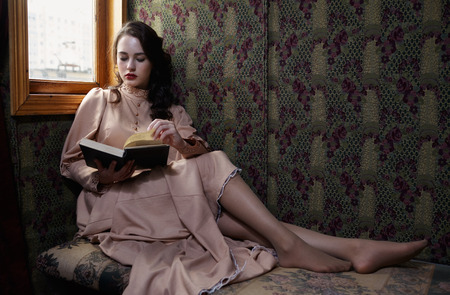 coupe: Young woman in beige vintage dress of early 20th century reading book in coupe of retro railway train
