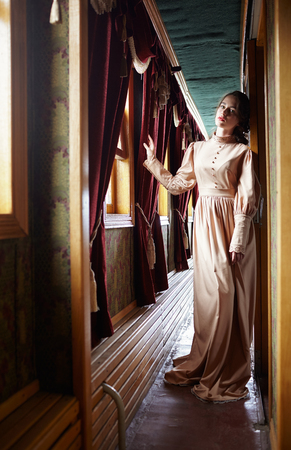 20th century: Young woman in beige vintage dress of early 20th century standing near window in corridor of retro railway train Stock Photo