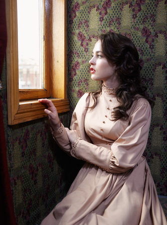 20th century: Young woman in beige vintage dress of early 20th century looking trough the  window in coupe of retro railway train