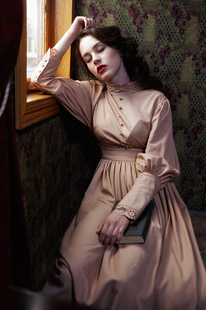 20th century: Young woman in beige vintage dress of early 20th century sleaping near window in coupe of retro railway train Stock Photo