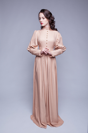 decollete: Full-length portrait of young beautiful woman in retro beige dress with day makeup and  green pistachio colour eyes Stock Photo