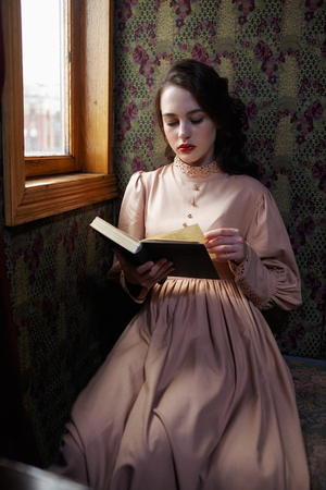 20th: Young woman in beige vintage dress of early 20th century reading book in coupe of retro railway train