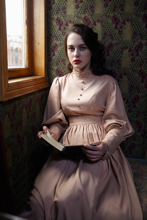 20th century: Young woman in beige vintage dress of early 20th century reading book in coupe of retro railway train