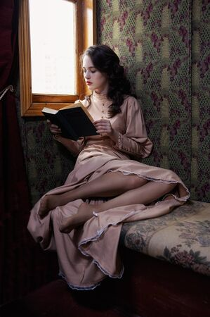 lady hand: Young woman in beige vintage dress of early 20th century reading book in coupe of retro railway train