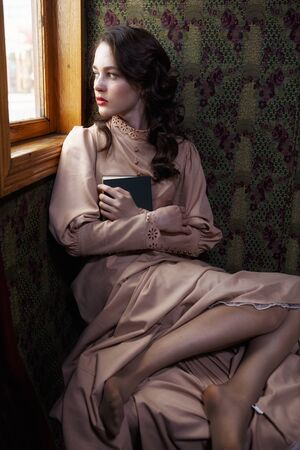 20th century: Young woman in beige vintage dress of early 20th century sitting near window in coupe of retro railway train