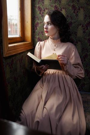 señora mayor: Mujer joven en vestido beige de época de principios del libro de lectura del siglo 20 en el coupé de tren de ferrocarril retro