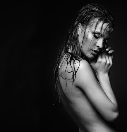 young woman nude: Portrait of young beautiful nude woman with wet shining  makeup and closed eyes on black background