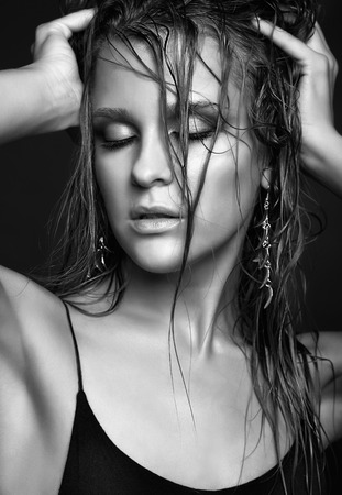wet hair: Portrait of young beautiful woman with wet shining  makeup and closed eyes on black background