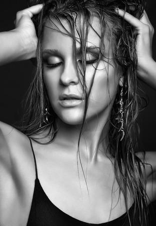 wet: Retrato de joven bella mujer con maquillaje brillante mojado y los ojos cerrados sobre fondo negro Foto de archivo