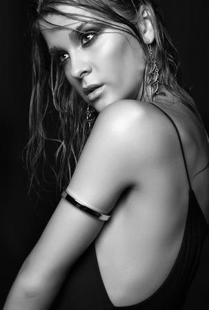 mojada: Retrato de joven bella mujer con maquillaje brillante húmedo sobre fondo negro Foto de archivo