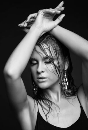 shy woman: Portrait of young beautiful woman with wet shining  makeup and closed eyes on black background