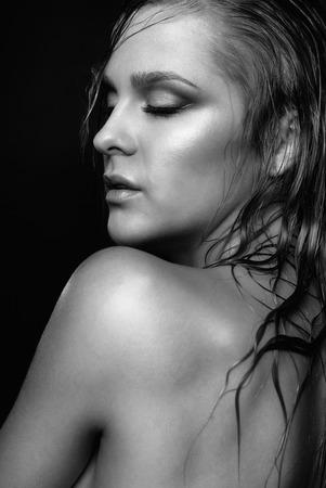 modelo desnuda: Retrato de joven bella mujer con maquillaje brillante mojado y los ojos cerrados sobre fondo negro Foto de archivo