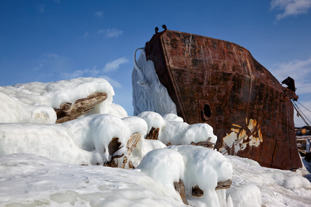 global cooling: Old frozen ship on the bank of Olkhon island on siberian lake Baikal at winter time