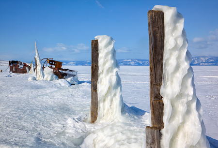 baical: Old frozen castaway ship on the bank of Olkhon island on siberian lake Baikal at winter time Stock Photo