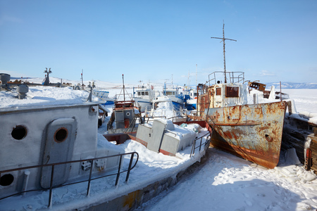 global cooling: Old frozen ships in the port of Olkhon island on siberian lake Baikal at winter time