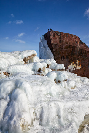 castaway: Old frozen castaway ship on the bank of Olkhon island on siberian lake Baikal at winter time Stock Photo