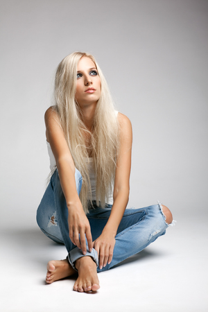 woman foot: Blonde young woman in ragged jeans and vest sitting on floor on gray background Stock Photo