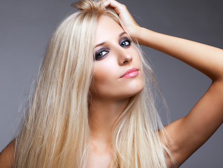gray eyes: Blonde young woman on gray background Stock Photo