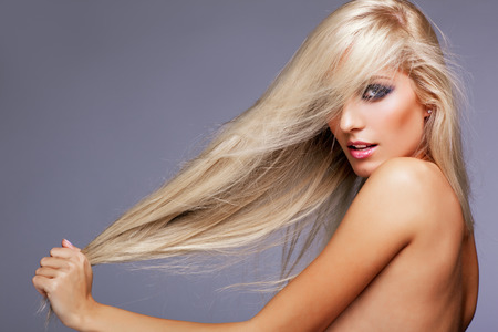 blond hair: Blonde young woman on gray background Stock Photo