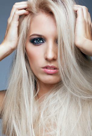 tousled: Blonde young woman on gray background Stock Photo