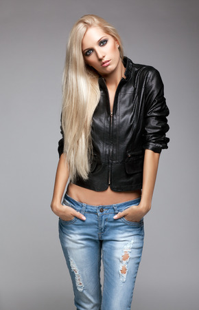 blue grey coat: Blonde young woman in ragged jeans and black jacket on gray background