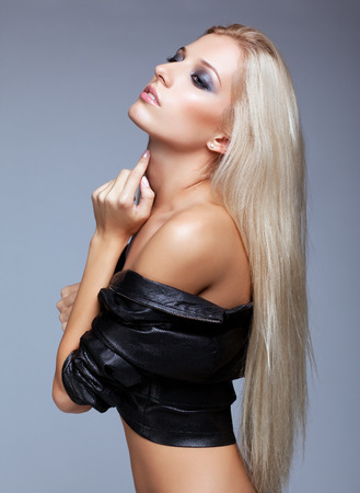 sexy girl posing: Blonde young woman in black jacket on gray background