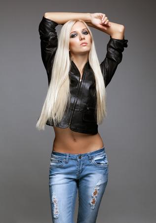 Blonde junge Frau in zerlumpten Jeans und schwarze Jacke auf grauem Hintergrund Standard-Bild - 47459895