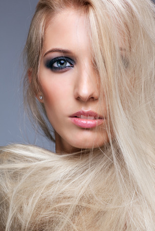 dishevelled: Blonde young woman on gray background Stock Photo