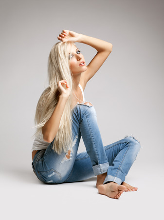 Blonde young woman in ragged jeans and vest sitting on floor on gray background Stock Photo